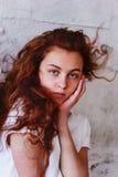 Pruebas modelo Muchacha hermosa del pelirrojo con el pelo rizado Color natural Retrato de Krupneishego en un fondo del ladrillo l Imagen de archivo