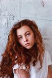 Pruebas modelo Muchacha hermosa del pelirrojo con el pelo rizado Color natural Retrato de Krupneishego en un fondo del ladrillo l Foto de archivo libre de regalías