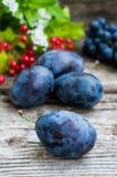 Prugne con l'uva su un fondo di legno Vista superiore Primo piano Fotografie Stock