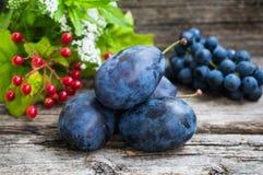Prugne con l'uva su un fondo di legno Vista superiore Primo piano Immagini Stock