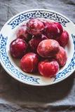 Prugne delle varietà differenti in un piatto ceramico bianco Fotografia Stock