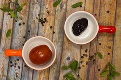 Prugne e pomodori marinati fogli di verde Immagini Stock