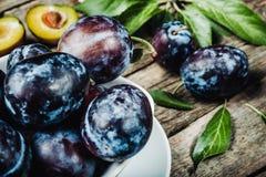 Prugne fresche con leaveson un fondo di legno scuro tonalità prescelto fotografia stock libera da diritti