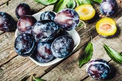 Prugne fresche con leaveson un fondo di legno scuro tonalità prescelto fotografia stock