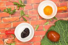 Prugne marinate in un piatto ceramico Mandarino in un piatto ceramico Immagine Stock