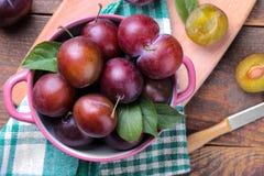 prugne mature con le foglie in una ciotola su una tavola di legno marrone Vista superiore fotografia stock