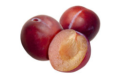 Prugne rosse fresche, in un taglio, su fondo bianco Fotografie Stock