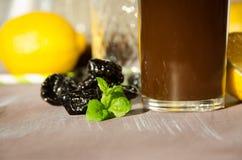 Prugne stufate con il bicchiere del limone Fotografia Stock Libera da Diritti