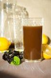 Prugne stufate con il bicchiere del limone Immagini Stock Libere da Diritti