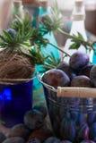 Pruimen in een emmer jam op een houten lijst die door bloemen wordt omringd Stock Foto