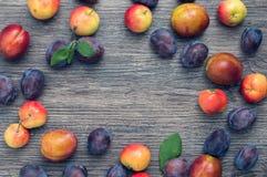 Pruimen en appelen op een houten oppervlakte hoogste mening De herfstachtergrond met vruchten en ruimte voor tekst royalty-vrije stock fotografie