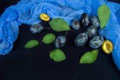 Pruimen en groene bladeren op een donkere achtergrond royalty-vrije stock foto
