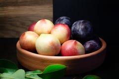 Pruimen en nectarines met bladeren op kleiplaat Stock Fotografie