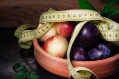 Pruimen en nectarines op kleiplaat met meetlint Royalty-vrije Stock Foto's