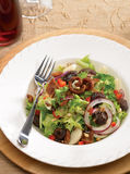 Prune and bacon salad. With red onion, red peppers,  pine nuts in a round plate with a fork Stock Photo