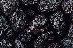 Prune close up background. Heap of glossy black prunes. Top view stock image