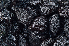 Prune close up background. Heap of glossy black prunes. Top view stock photo