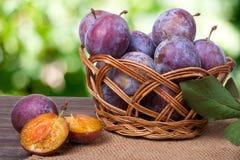 Prune dans un panier en osier sur la table en bois avec la toile à sac et le fond vert brouillé Photo stock