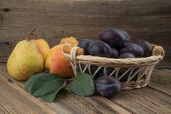 Prune dans un panier en osier sur le fond en bois image libre de droits