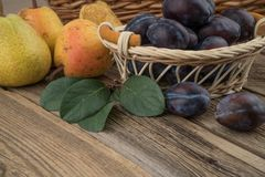 Prune dans un panier en osier sur le fond en bois photographie stock libre de droits