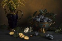 Prune dans un vase sur une table avec des fleurs Photo libre de droits
