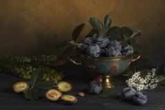 Prune dans un vase sur une table avec des fleurs Image libre de droits