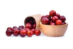 Prune de cerise rouge dans le panier en bois et cuvette d'isolement sur le blanc Photographie stock libre de droits