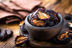 Prune, dried plums fruits on dark rustic wooden background Royalty Free Stock Images