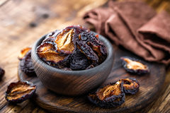 Prune, dried plums fruits on dark rustic wooden background Stock Images