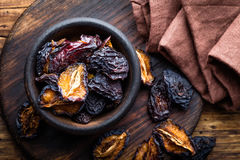 Prune, dried plums fruits on dark rustic wooden background Stock Photo
