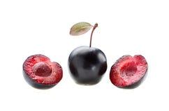 Prune entière avec deux moitiés et os d'isolement sur un backgrou blanc Photos stock
