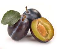 Prune et une moitié et feuilles Photo stock