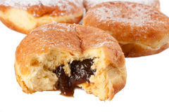 Prune filled Paczek. Four Paczki or Polish doughnuts, one with the prune filling spilling out Stock Images