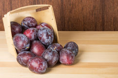 Prune plums spilling from wooden container Stock Photo