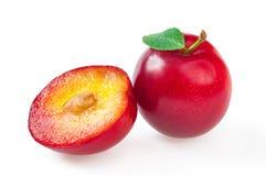 Prune rouge délicieuse mûre avec la feuille, et demi prune de coupe plan rapproché, Photographie stock libre de droits