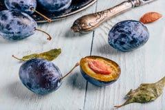 Prunes avec les feuilles et le couteau au-dessus de la surface en bois photographie stock libre de droits