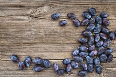 Prunes bleues fraîches sur la vieille table en bois Aliment biologique Vue supérieure images stock