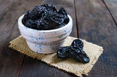 Prunes in a ceramic bowl on a dark wooden background. Dried fruits stock image