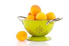 Prunes in colander. Yellow prunes in green colander Stock Photography
