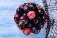 prunes délicieuses mûres dans un panier en osier sur une table en bois bleue Vue supérieure images libres de droits