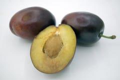 Prunes d'isolement Totalité et une moitié du fruit bleu de prune d'isolement sur le fond blanc, avec le chemin de coupure, Photo libre de droits