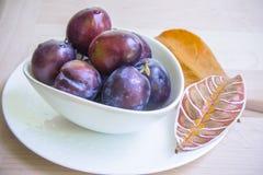 Prunes dans la cuvette avec une paire de feuilles peintes Photo libre de droits