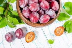 Prunes dans la cuvette en bois avec les feuilles vertes sur la table Photographie stock libre de droits