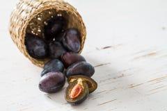 Prunes dans le panier, fond en bois blanc Photographie stock