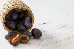 Prunes dans le panier, fond en bois blanc Photographie stock libre de droits