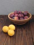 Prunes dans un plat sur la vieille table en bois Photo stock