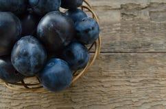 Prunes de jardin dans un panier en osier sur un fond en bois Photographie stock