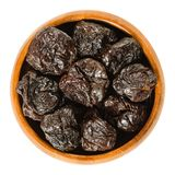Prunes, dried plums in wooden bowl over white. Prunes, dried plums in wooden bowl. Uncooked, dehydrated, pitted fruits of Prunus domestica with black color, used royalty free stock image