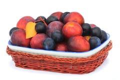 Prunes et pruneaux dans un vase pour le fruit sur un fond blanc. Photographie stock