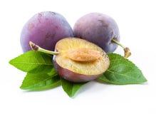 Prunes et une moitié avec des feuilles photo stock